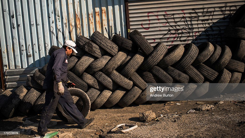 A man organizes a pile of tires on June 17, 2013 in the Willet's Point neighborhood of the Queens borough of New York City. The Willet's Point Neighborhood, also known as the Iron Triangle, is situated directly next to Citi Field, where the Met's play baseball, and is known for both its car repair shops and lack of paved roads. The future of the neighborhood has been a contentious issue between residents and the city, as the city hopes to further develop the land despite protests from its residents.