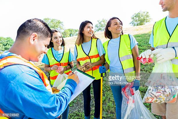 Man organizes group of volunteers during community cleanup