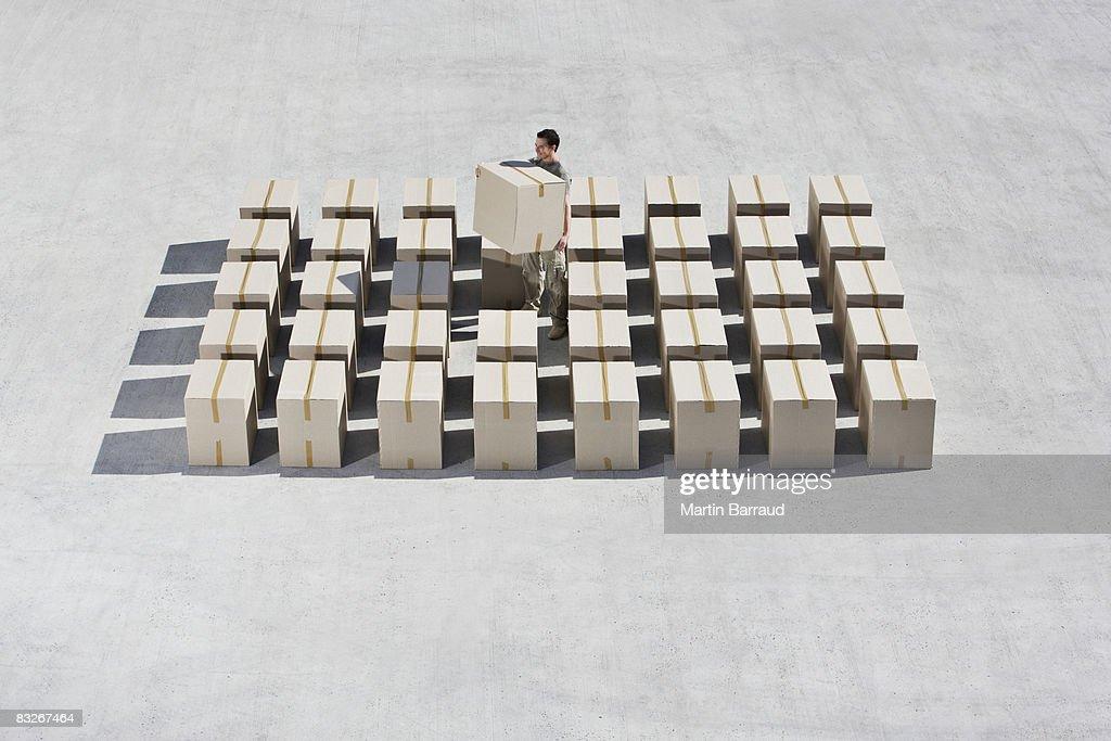 Man organizing boxes on sidewalk : Stock Photo