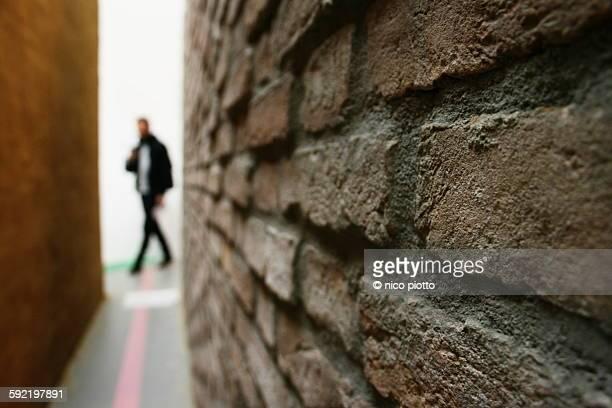 Man out of focus walking near a brick wall