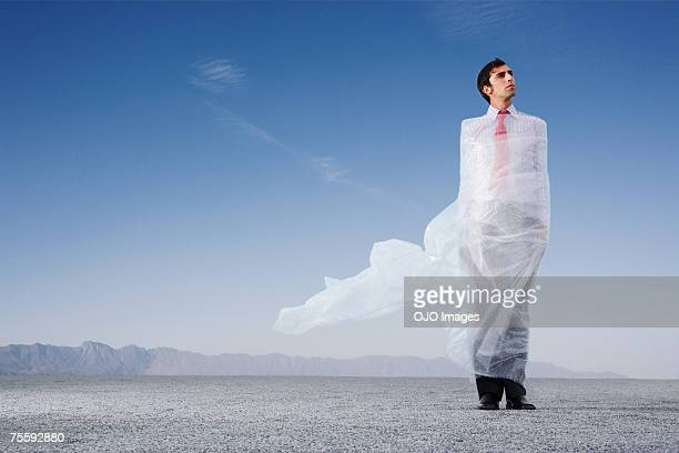 Man outdoors ensnared in a sheer sheet