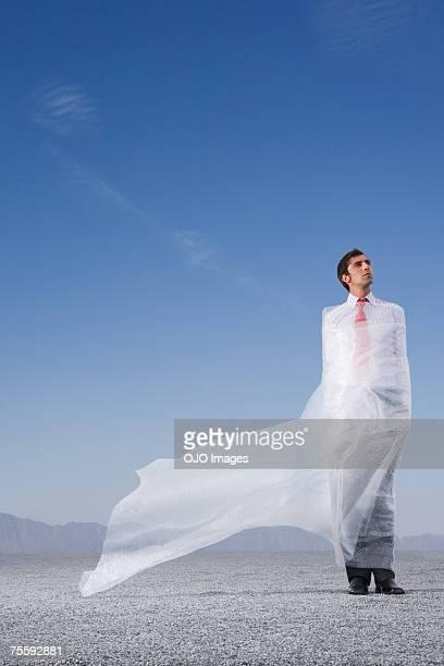 Man outdoors ensnared in a sheer sheet