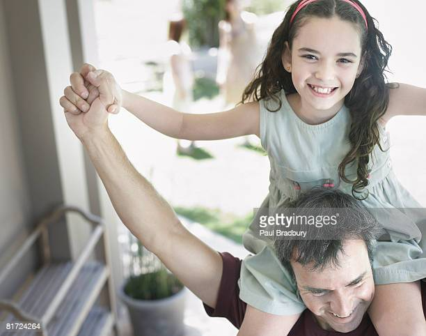Man outdoors giving young girl shoulder ride