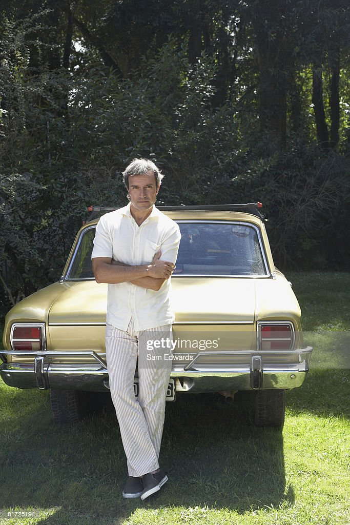 Man outdoors leaning on car : Stock Photo