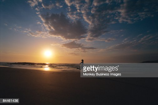 Man outdoors running on a beach at sunset (silhouette) : Stock Photo