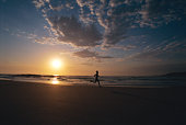 Man outdoors running on a beach at sunset (silhouette)