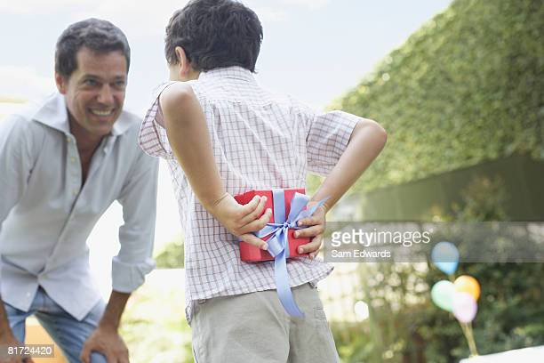 Man outdoors smiling with young boy hiding gift behind his back