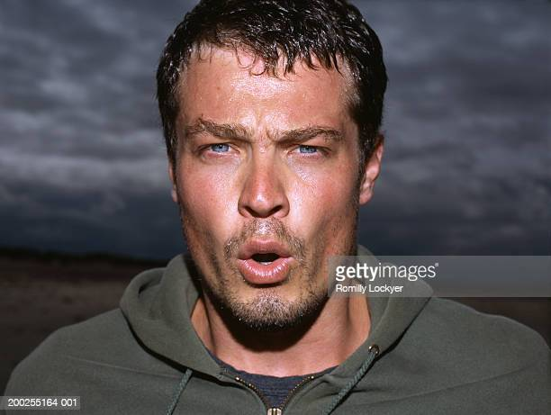 Man outdoors, sweating and breathing heavily, portrait, close-up