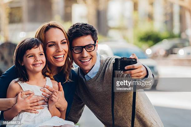Man outdoors taking a selfie of his family with digital camera
