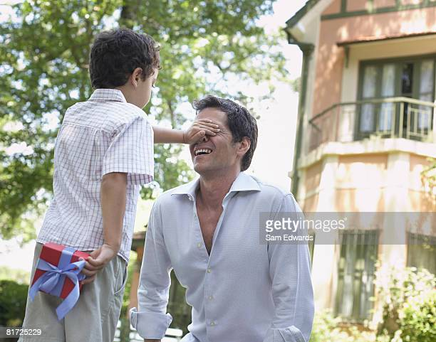 Man outdoors with young boy covering his eyes and hiding gift behind his back