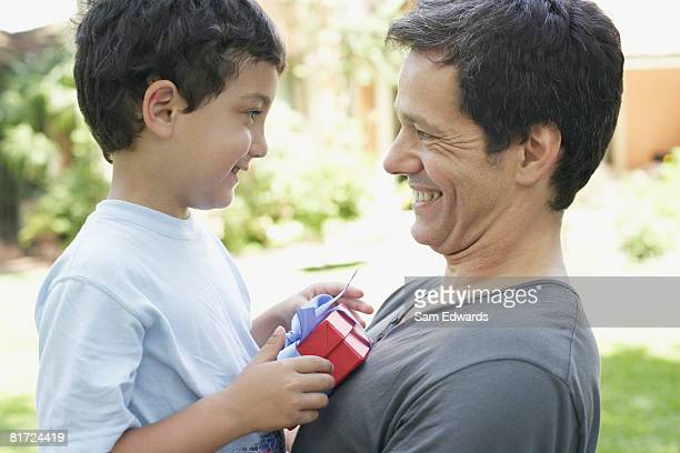 Man outdoors with young boy holding gift and smiling