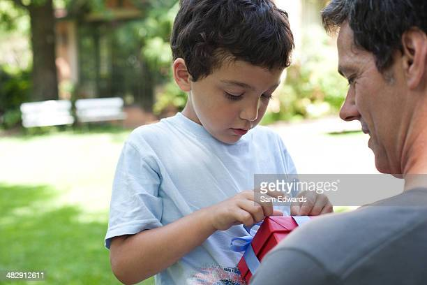 Man outdoors with young boy holding gift