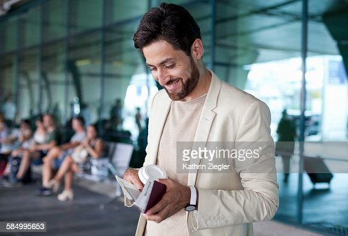 man outside airport, passport in hand