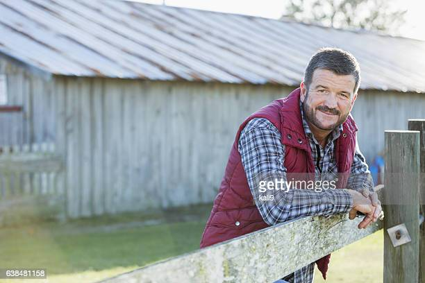 Man outside barn leaning on wooden fence