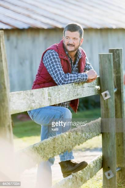 Man buiten schuur leunend op houten hek