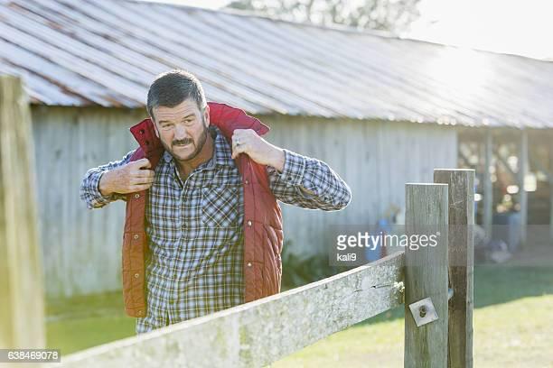 Man outside barn putting on jacket