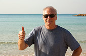 Portrait of a man over 60 years old. Elder man shows gesture - all right. Hi was shot close-up against the sea on a Sunny day. The man is wearing sunglasses and a t-shirt. Hi in good physical shape, h