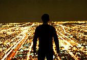 Man Overlooking City at Night