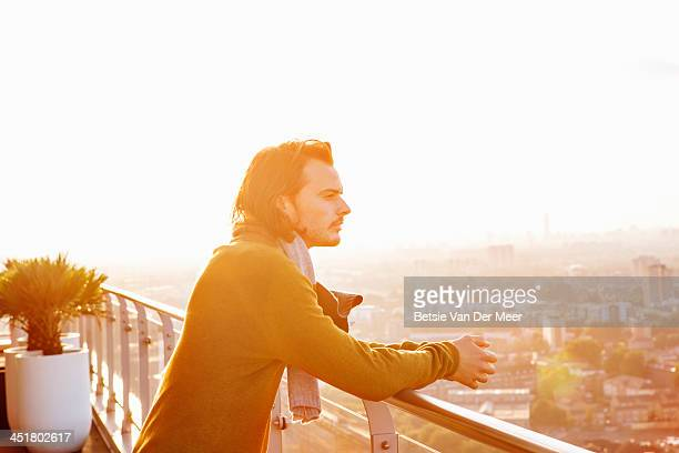 Man overlooks city at sunset.