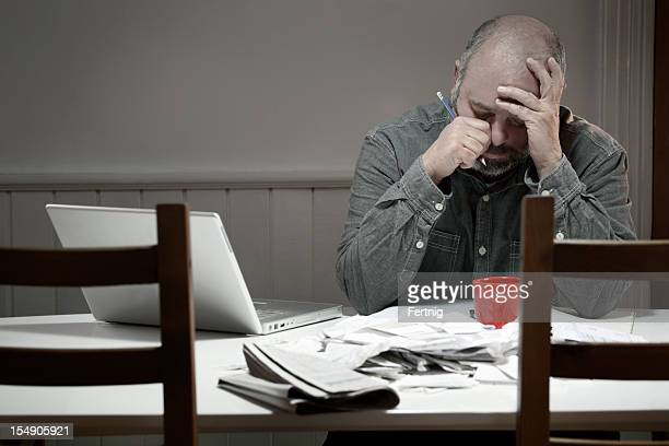 Man overwhelmed with bills, debts, taxes or bookkeeping