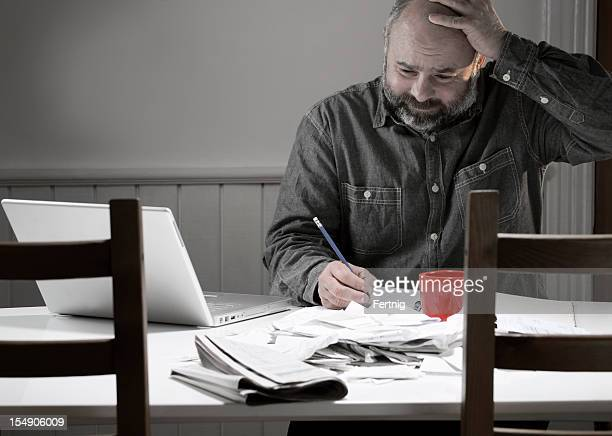 Man overwhelmed with bills, taxes or bookkeeping