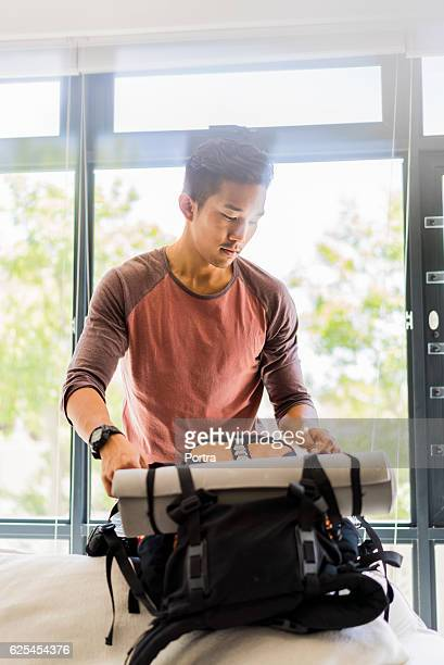 Man packing bag while standing against window