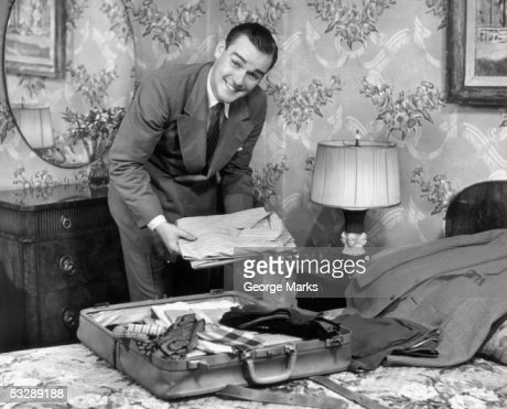 Man packing clothes into luggage : Stockfoto