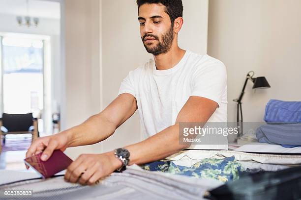Man packing for vacation in bedroom