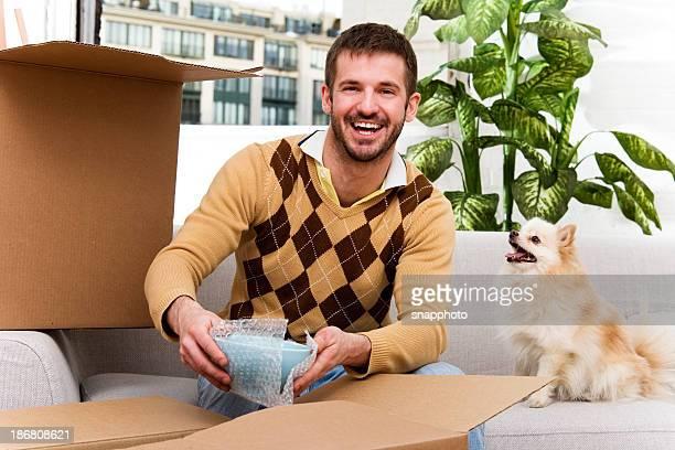 Man Packing or Unpacking at home.  Pomeranian Helping