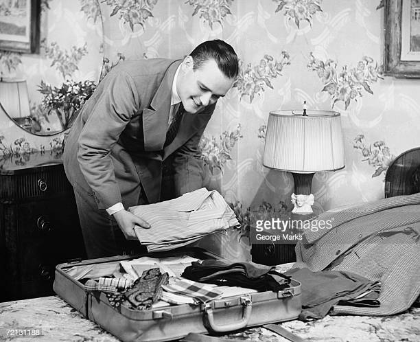 Man packing suitcase in bedroom (B&W)