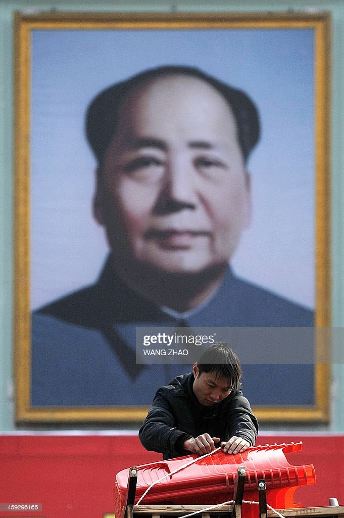 A man packs chairs in front of a portrait of former Chinese leader Mao Zedong in Shaoshan, in China's central province of Hunan on December 25, 2013. Thousands of admirers of Communist China's founder Mao Zedong flocked to his home town on December 25 to bow before his graven image -- including one statue of solid gold -- before the 120th anniversary of his birth.
