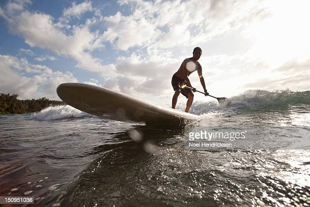 A man paddle boards in the ocean
