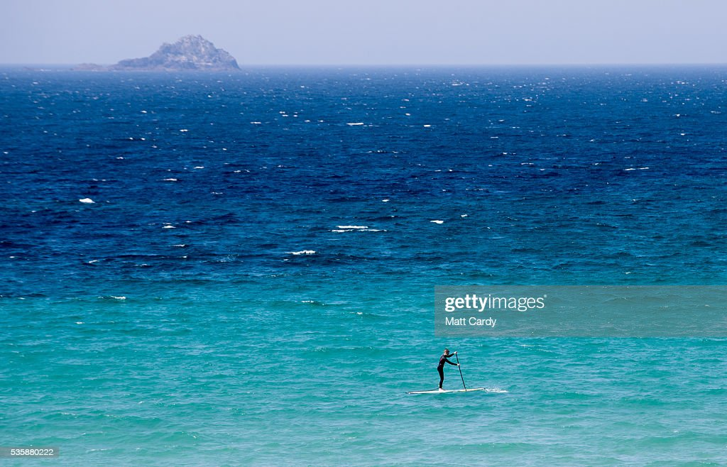A man paddleboards as people enjoy the fine weather at Sennen Cove on May 30, 2016 in Cornwall, England. As some parts of the UK were bathed in sunshine for the bank holiday weather forecasters have warned that gale-force winds and thunderstorms will sweep in from the east overnight.