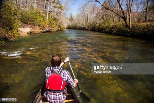 A man paddles a canoe down the calm Chattahoochee River in North Georgia.