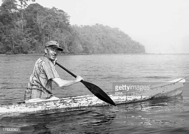 A man paddles a dugout canoe at Club de Pesca in Pinas Bay Panama circa 1960