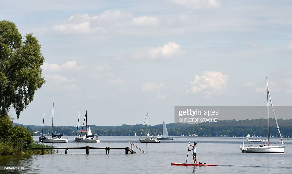 A man paddles on a board at lake Ammersee near the small Bavarian village Utting, southern Germany, on June 28, 2016. Meteorologists forecast a warm and sunny weather during the next days for the southern German region. / AFP / CHRISTOF