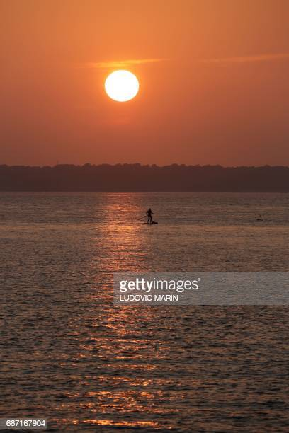 A man paddles on Arcachon Bay near Cap Ferret at sunset on April 10 2017 off the coast of Arcachon / AFP PHOTO / LUDOVIC MARIN