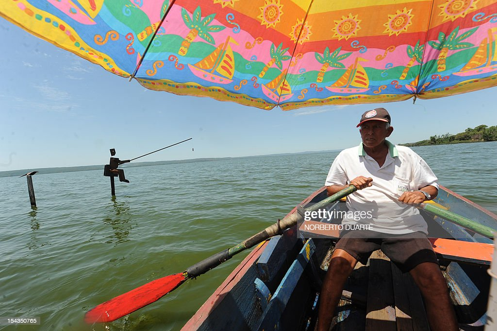 A man paddles on his boat across the Ypacarai Lake, declared not suitable for bathing, in Ypacarai, Paraguay on October 18, 2012. Paraguay's Health Minister Antonio Corbo said that water samples from the lake analized in Sao Paulo, Brazil with the backing of the Pan American Health Organization determined that the bacteria found in the lake's waterweed present a high level of neurologic and liver toxicity.
