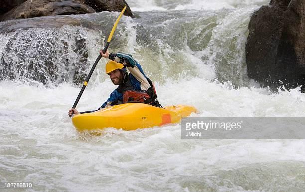 Hombre remo un blanco de agua en Kayak por el río de Idaho.