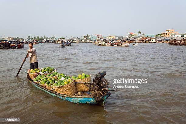 Man paddling boat loaded with papayas at Cai Rang Floating Market.