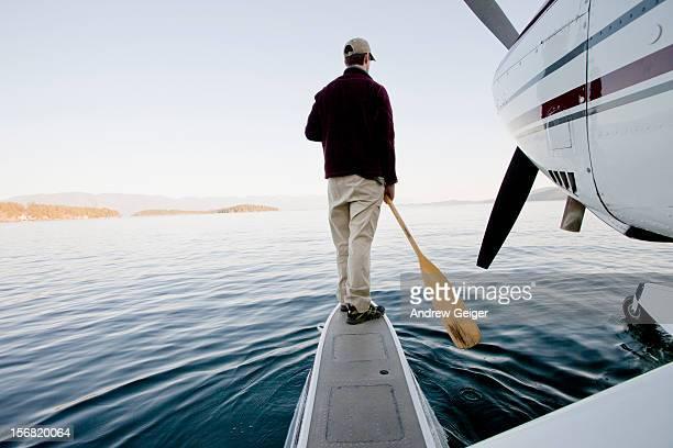 Man paddling float plane on lake.
