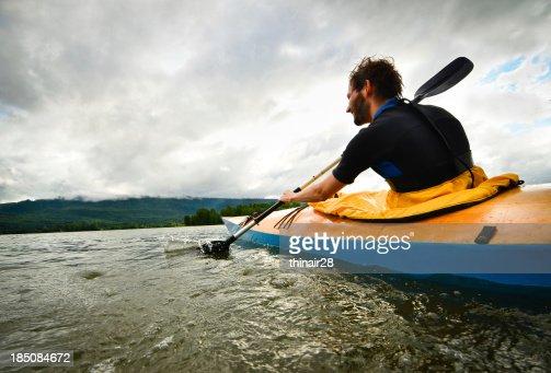 Man paddling in wooden kayak