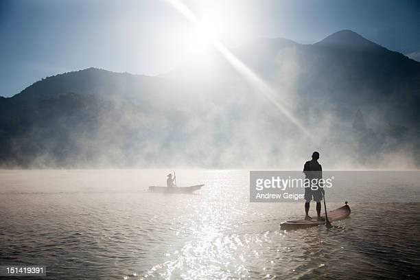 Man paddling iSUP on misty lake at sunrise