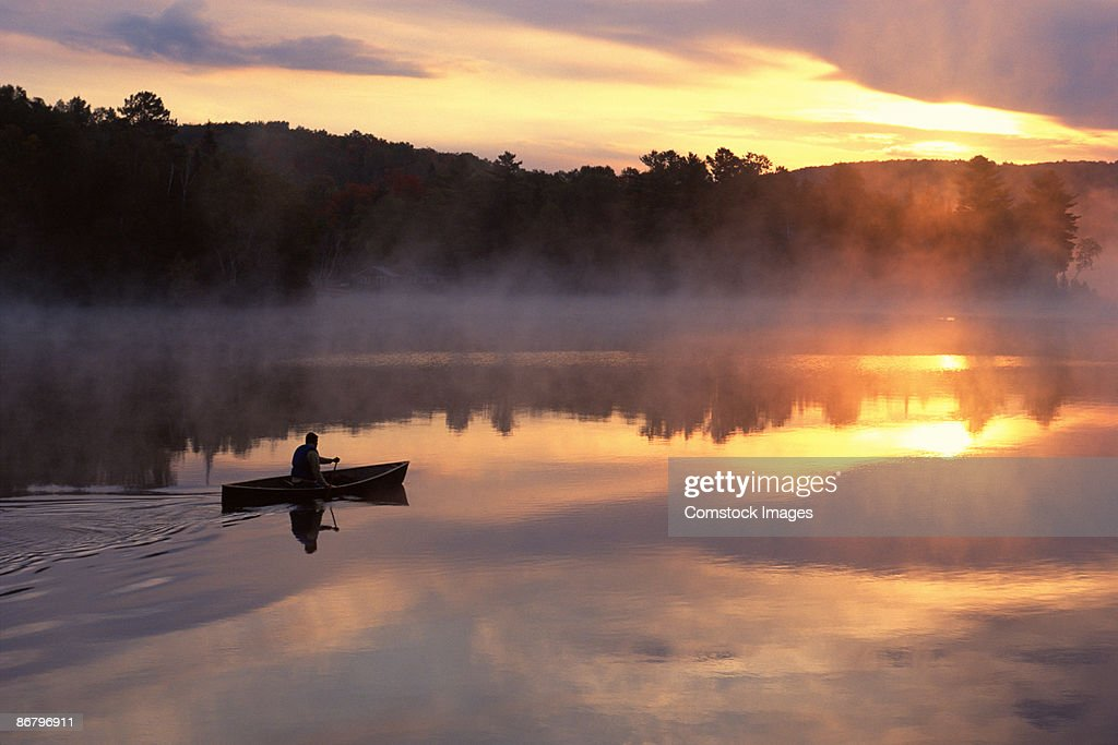 Man paddling solo canoe on Oxtongue Lake