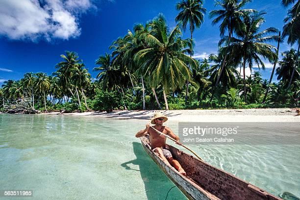 Man paddling wooden pirogue