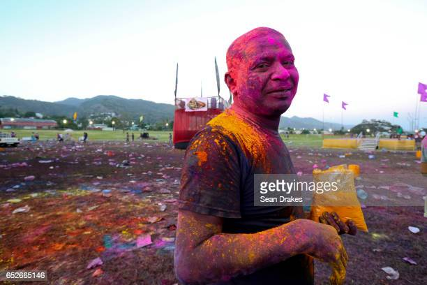 A man painted with colorful abeer powder poses during Holi which celebrates the arrival of the season of Spring as part of the annual Phagwah...