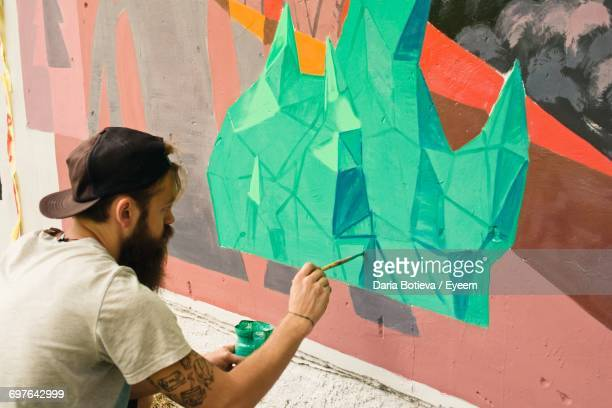Man Painting A Mural On The Wall