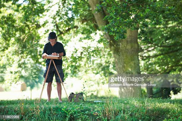 Man painting a picture in a park