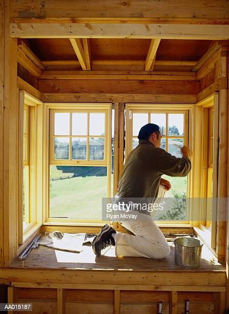 Man painting bay window frame