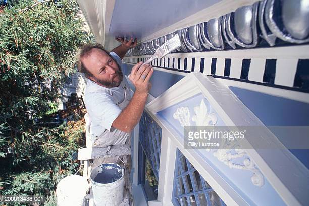 Man painting decorative molding on house exterior